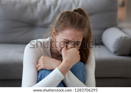 Desperate upset teen girl victim crying alone at home, sad abused young woman in tears feeling depressed heartbroken offended bad having problems, unexpected pregnancy, regret mistake abortion #1283706295