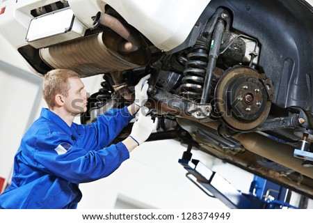 car mechanic inspecting car wheel and suspension detail of lifted automobile at repair service station #128374949