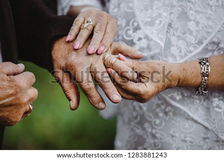 elder couples hands put on the wedding rings on each other.  elderly couple wedding.gold couple  is getting married. elder couples hand exchange the rings. wedding anniversary. golden wedding concept. #1283881243