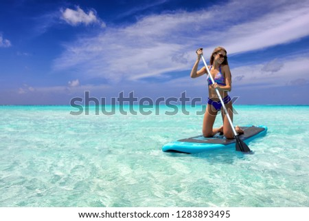 Attractive woman in bikini on a Stand Up Paddle (SUP) board over tropical, turquoise sea