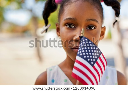 Portrait of a young girl holding an American flag.