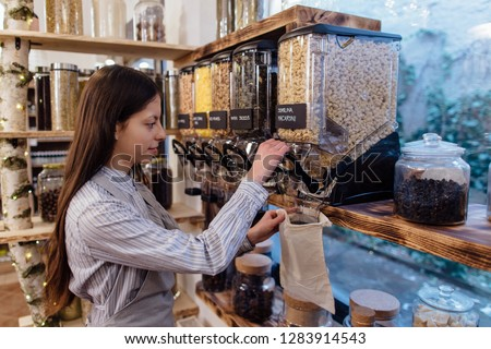 Shop assistant filling reusable bag with dried pasta in organic grocery store. Young shopkeeper working in zero waste shop. Royalty-Free Stock Photo #1283914543