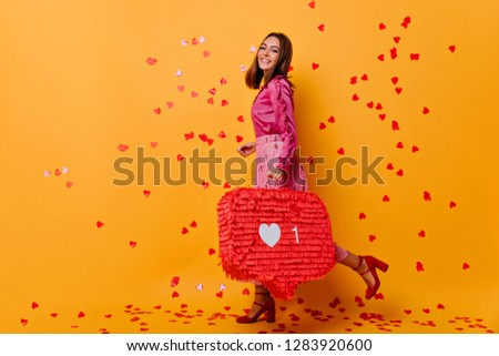Stylish appealing girl posing in studio with inspired smile. Jocund female blogger in pink blouse laughing under confetti. #1283920600