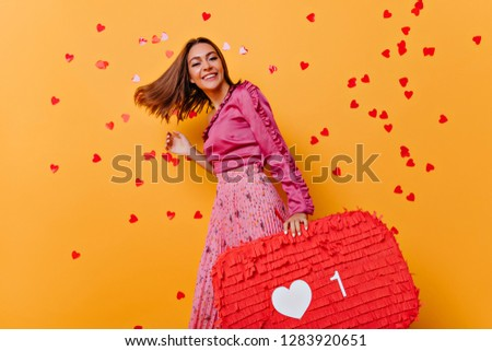 Funny girl in pink blouse dancing in studio. Amazing caucasian model enjoying photoshoot with confetti. #1283920651