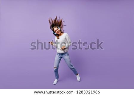 Cheerful, slightly crazy girl playing imaginary guitar, listening to big headphones in big headphones. Studio portrait of musician with dark hair flying #1283921986