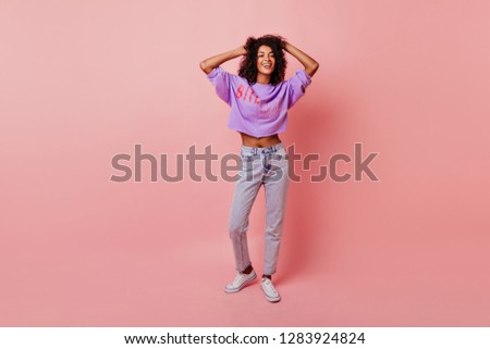 Full-length portrait of lovely slim woman touching her soft black hair. Blithesome african girl in jeans dancing on rosy background. #1283924824