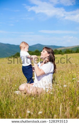 Family - happy mom and her son smiling at nature #128393513