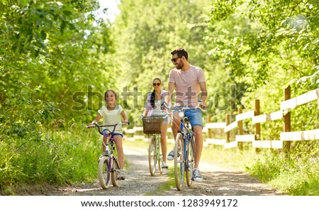 family, leisure and people concept - happy mother, father and little daughter riding bicycles in summer park #1283949172