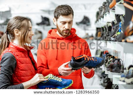 Mam and woman in red sports clothes choosing trail shoes for hiking standing near the showacase of the modern sports shop #1283966350