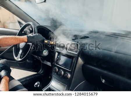 Carwash, worker cleans salon with steam cleaner Royalty-Free Stock Photo #1284015679