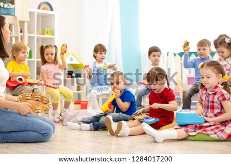 Kindergarten children playing different musical toys. Early musical education in day care centre #1284017200