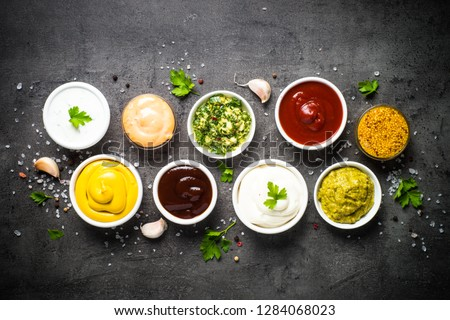 Set of sauces - ketchup, mayonnaise, mustard soy sauce, bbq sauce, pesto, chimichurri, mustard grains and pomegranate sauce on dark stone background. Top view copy space. #1284068023