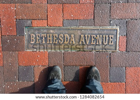 A sign on the ground labels Bethesda Avenue, a popular street for shopping and restaurants in the Chevy Chase neighborhood in Montgomery County.  #1284082654