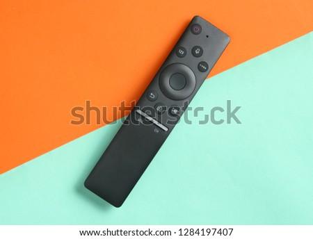 Modern TV remote control on orange blue background. Top view, minimalism #1284197407