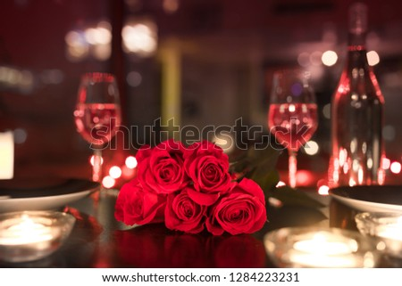 Red roses and candle lights in a romantic restaurant setting.  #1284223231