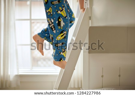 Young boy climbing up the ladder of bunks beds.