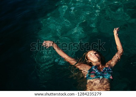 Woman swimming relaxing in tropical swimming pool outdoor. Summer sunny  day