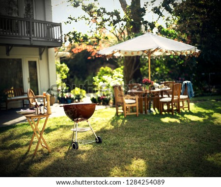Outdoor dining table and barbeque grill in the back yard of a house.