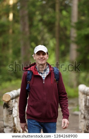 Man with backpack at wooden bridge in a forest #1284268900