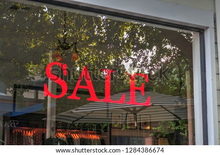 Red Sale Sign Painted on Storefront Window of a Local Business Having a Sale