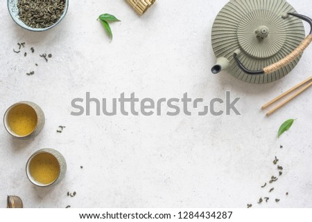 Asian Tea Set -  iron teapot and ceramic teacups with green tea and leaves. Traditional tea composition on white background, copy space, top view. #1284434287
