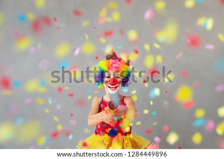Funny kid clown with party poppers. Happy child playing at home. 1 April Fool's day concept #1284449896