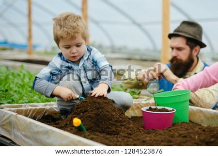 eco garden. eco garden workers of father and son. eco garden cultivation. family works in eco garden. flowers presentation #1284523876