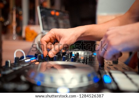 control DJ for mixing music with blurred people dancing at party in nightclub #1284526387