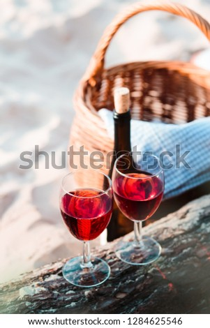 Two wine glasses with red wine standing on tree trunk, on beach, beside wicker basket with bottle of wine #1284625546