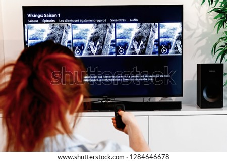 Benon, France - December 30, 2018: Woman holding a tv remote control In the process of selecting the viking success series proposed by Prime Video, a video-on-demand service created by Amazon.com #1284646678