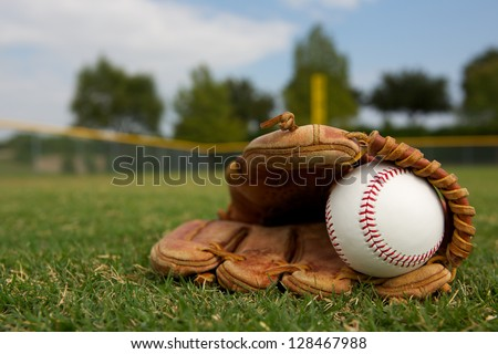 New Baseball in a Glove in the Outfield Royalty-Free Stock Photo #128467988