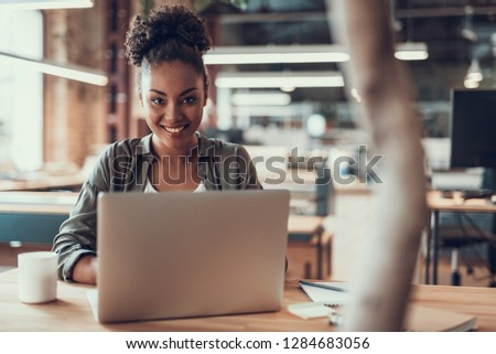 Portrait of charming young lady sitting at table with notebook and cup of coffee. She is looking at camera and smiling #1284683056