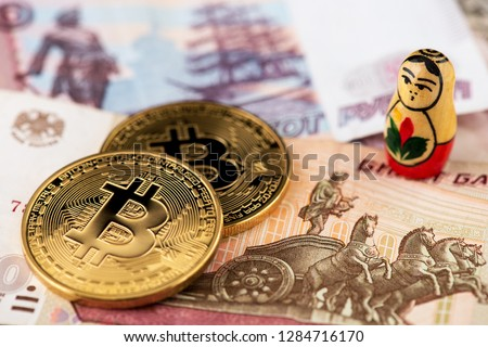 Bitcoin coins on Russian banknotes with russian national doll A close up image of bitcoins with Russian rubles banknotes Bitcoin coin on the background of Russian rubles Bitcoin Russia Ruble Crypto #1284716170