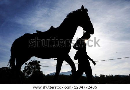 silhouetted of man and horse walking early morning  #1284772486