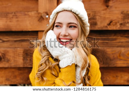 Portrait of a smiling girl in cute warm clothes touching her face and curly hair and looking to the left #1284816175