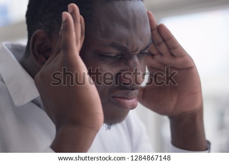 portrait of stressed sick black man with headache; ill african man suffers from headache, vertigo, dizziness, migraine, stress, depression, hangover concept; adult african man model #1284867148