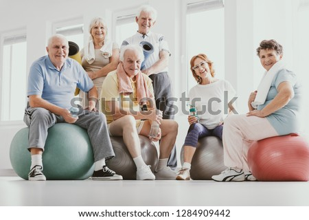 Group of active seniors sitting on exercising balls in modern fitness center after sport's training #1284909442