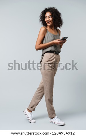 Full length of a happy young african woman casually dressed standing isolated over gray background, holding mobile phone #1284934912