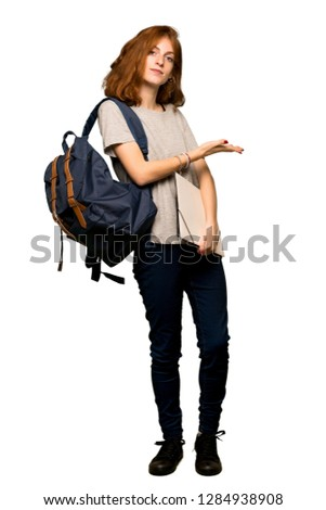 A full-length shot of a Young redhead student presenting an idea while looking smiling towards over isolated white background #1284938908