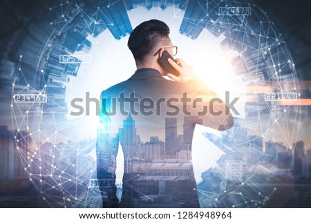 The double exposure image of the businessman using a smartphone during sunrise overlay with cityscape image. The concept of modern life, business, city life and internet of things. #1284948964