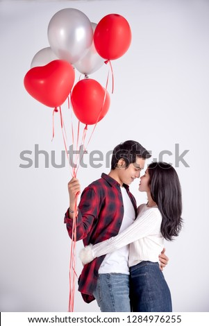 Beautiful Young couple at home,enjoy spend time,kiss and hug together in celebration Saint Valentine's day,hand hold  red and gray balloon heart gift,happy and love motion. #1284976255