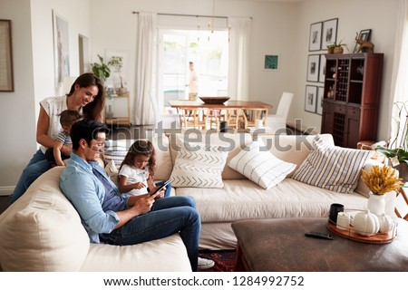 Young Hispanic family sitting on sofa reading a book together in their living room #1284992752