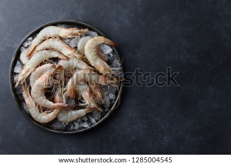 Fresh tiger prawns in a plate with ice on black textured background, top view #1285004545