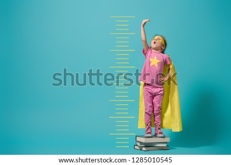 Little child playing superhero. Kid measures the growth on the background of bright blue wall. Girl power concept. Yellow, pink and  turquoise colors. #1285010545