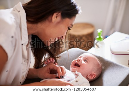 Happy four month old baby boy lying on changing table looking up at his mum, close up #1285054687