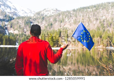 hiker with red sweater and flag from the european union outdoor somewhere in the austrian alps #1285059991