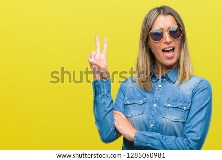 Young beautiful woman wearing sunglasses over isolated background smiling with happy face winking at the camera doing victory sign. Number two. #1285060981