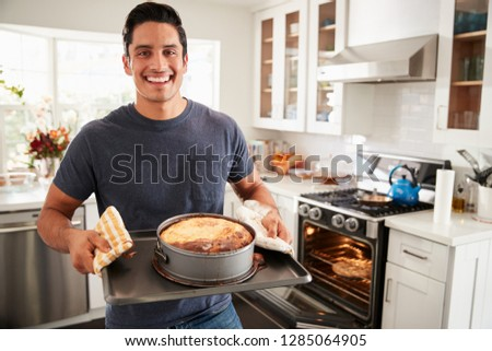 Smiling millennial Hispanic man standing in kitchen presenting the cake he has baked to camera Royalty-Free Stock Photo #1285064905