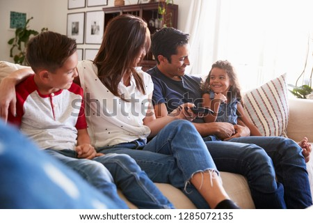 Young Hispanic family sitting on the sofa at home to watch TV, looking at each other, close up #1285072135