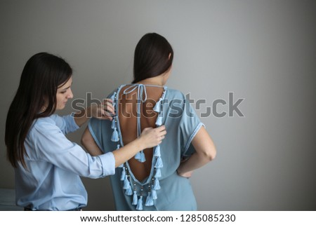 two caucasian women trying on a tunic, fancy handmade clothes. Small business and sewing production #1285085230